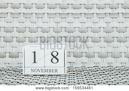 Closeup surface white wooden calendar with black 18 november word on blurred weave wood chair textured background with copy space selective focus at the calendar