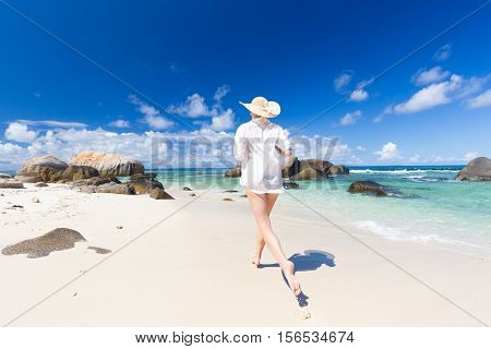 Active woman wearing white loose tunic over bikini and beach hat, enjoying amazing white sandy beach on Mahe Island, Seychelles. Summer vacations on picture perfect tropical beach concept.