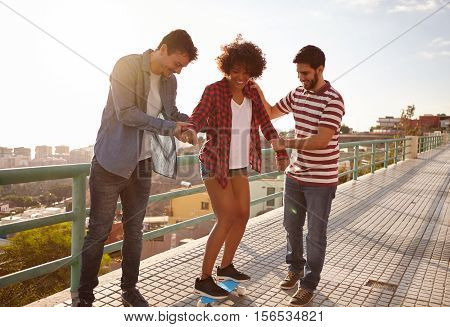 Boys Teaching A Girl To Skateboard