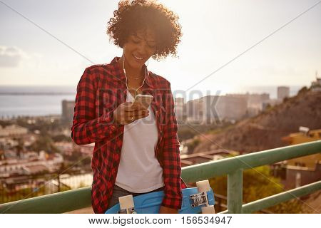 Girl With Toothy Smile Looking At Cellphone