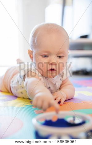 Baby girl with blue eyes playing on the floor with toys on a playmat. A cute young child plays.