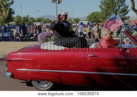 Surprise, AZ, USA - NOV. 11: One male Navy veteran sitting on top of the seat in the back of a red convertible with white interior and an American flag attached to the windshield waving towards the crowd at the city of Surprise, Arizona Veteran's Day Para