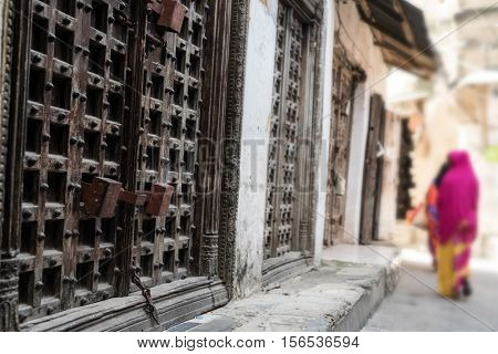 typical Zanzibar town street with old iron doors and wooman walking away, Africa