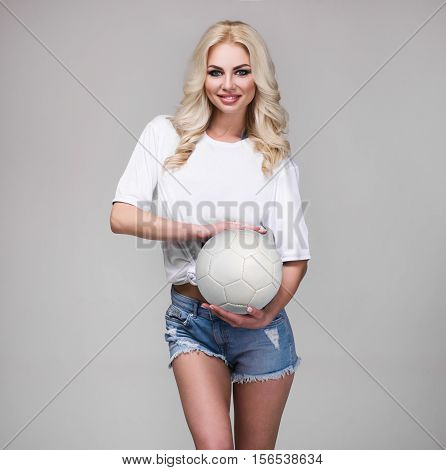 Woman In Shorts Holding Foot Ball On Gray Background