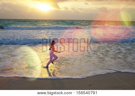 silhouette of woman running along the edge of sea on a sunset