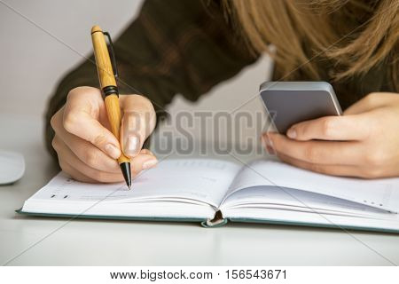 Girl copying infromation from smartphone to notepad. Close up