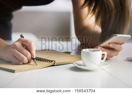 Female copying infromation from smartphone to notepad. Close up