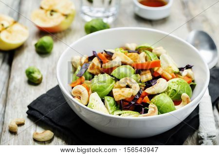 Brussels sprouts red cabbage carrot cashew apple salad with maple syrup olive oil dressing.
