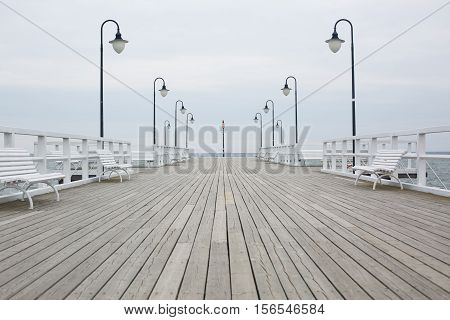 wooden pier on the sea coast with white lights and benches