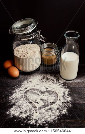 Home baking. Baking with love. Baking ingredients and heart of flour on the wooden dark table