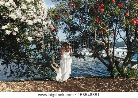 bride in dress near the sea and blooming trees in Montenegro