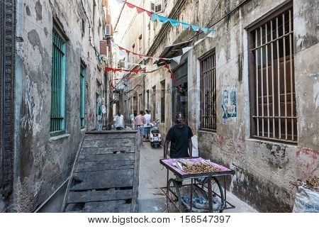 Stone Town, Zanzibar - July, 14, 2016: Editorial use - typical narrow street in Zanzibar town with workers and tourists