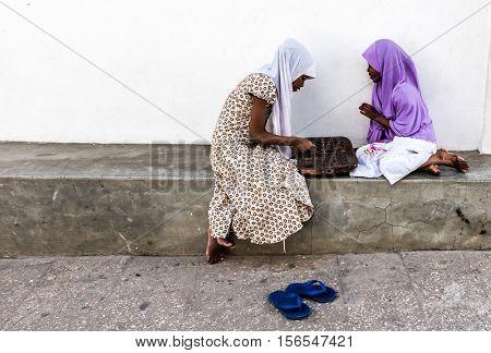 Stone Town, Zanzibar - July, 14, 2016: Editorial use - two Zanzibar girls playing board game on a street, Africa