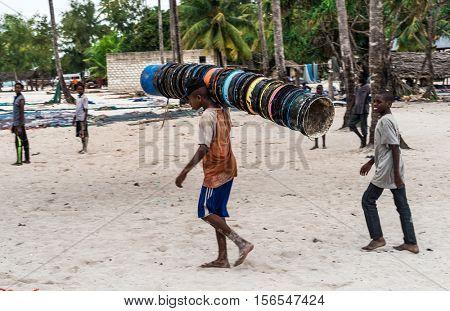 Zanzibar, Tanzania - July, 14, 2016: Editorial use - young african boy carrying many buckets on his shoulder on Zanzibar street