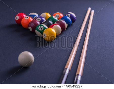 Blue billiard table with balls and cues.