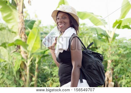smiling young woman carrying a bag on her back.