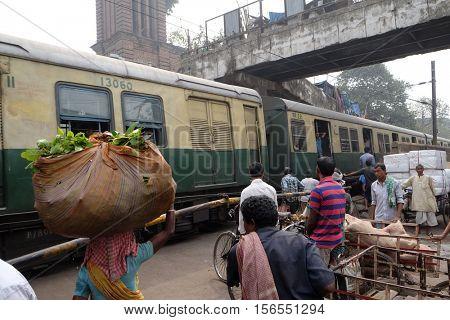 KOLKATA, INDIA - FEBRUARY 10: Pedestrians, rickshaws, cyclists waiting on railroad crossing in Kolkata, India on February 10, 2016.