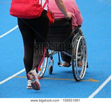 Wheelchair With An Attendant On The Athletic Track During The Sp