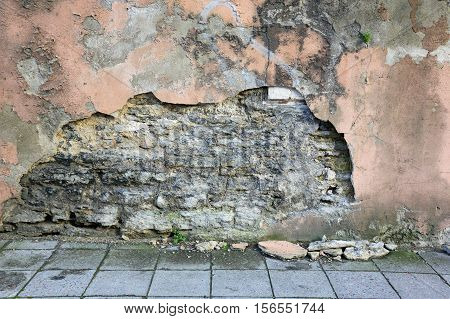crumbling plaster on the wall of an old house