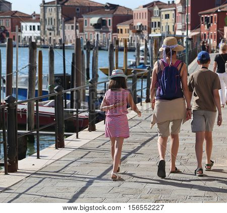 Mom And Two Children Walking On The Island Of Murano Near Venice