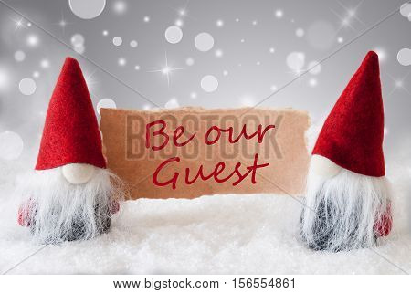 Christmas Greeting Card With Two Red Gnomes. Sparkling Bokeh And Noble Silver Background With Snow. English Text Be Our Guest