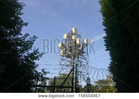 Metal telecommunications mast with aerials and dishes. Background of blue sky with white aircraft contrails. Surrounded by a security fence with trees.