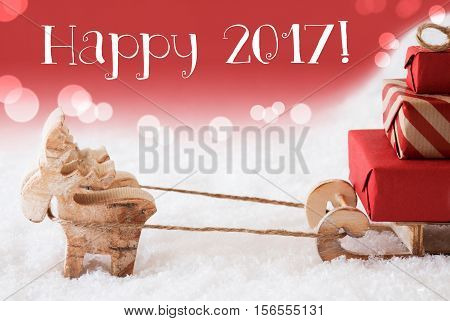 Moose Is Drawing A Sled With Red Gifts Or Presents In Snow. Christmas Card For Seasons Greetings. Red Christmassy Background With Bokeh Effect. English Text Happy 2017 For Happy New Year
