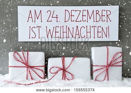 Label With German Text Am 24. Dezember Ist Weihnachten Means December 24th Is Christmas Eve. Three Christmas Presents On Snow. Cement Wall As Background With Snowflakes. Modern And Urban Style.