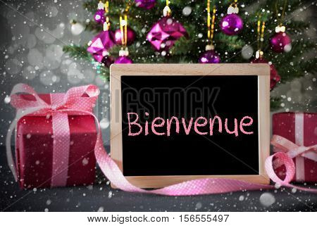 Chalkboard With French Text Bienvenue Means Welcome. Christmas Tree With Rose Quartz Balls, Snowflakes And Bokeh Effect. Gifts Or Presents In The Front Of Cement Background.