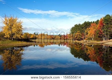 Vibrant autumn leaves and colors of fall tree foliage reflect on the waters of Lake Sabago Maine in October.