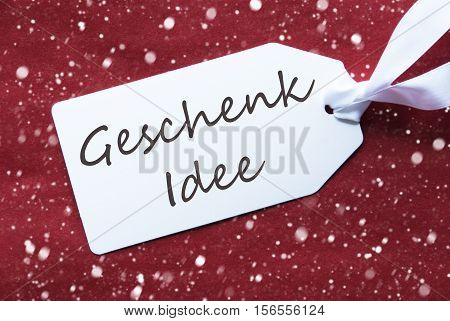 German Text Geschenk Idee Means Gift Idea. One White Label On A Red Textured Background. Tag With Ribbon And Snowflakes.