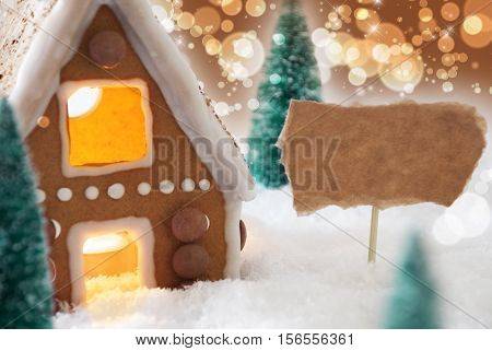 Gingerbread House In Snowy Scenery As Christmas Decoration. Christmas Trees And Candlelight For Romantic Atmosphere. Bronze And Orange Background With Bokeh Effect. Copy Space For Advertisement