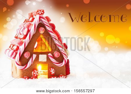 Gingerbread House In Snowy Scenery As Christmas Decoration. Candlelight For Romantic Atmosphere. Golden Background With Bokeh Effect. English Text Welcome