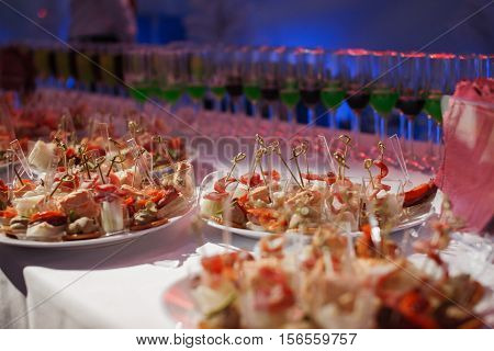 Catering banquet table with baked food snacks, sandwiches, cakes, cups and plates, self serve, open buffet dinner.