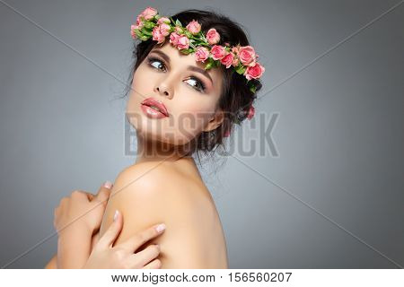 Beautiful young girl with a chaplet from roses in hairs, emotions, cosmetics,on a light- grey background