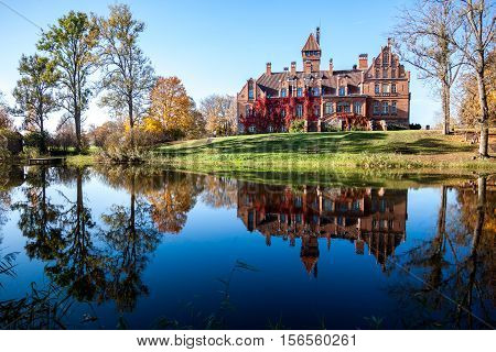 Brick castle at pond in an autumn season.
