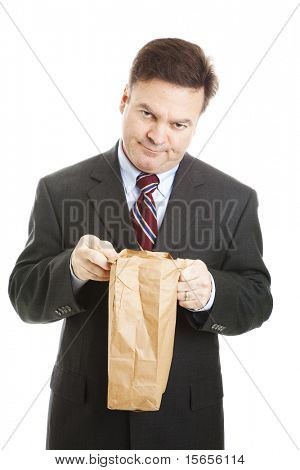 Disappointed businessman having to bring his lunch in a bag to save money.  Isolated.