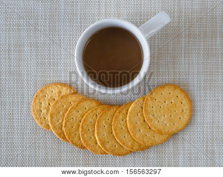 Cup of coffee and biscuit on sackcloth and wooden table