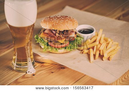 Fish and Chips Burger with fried potato straw, fresh salad and cold beer