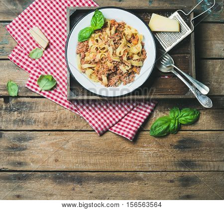 Italian pasta dinner. Homemade Tagliatelle Bolognese with Parmesan cheese and fresh basil leaves in wooden tray over rustic wooden background, top view, copy space
