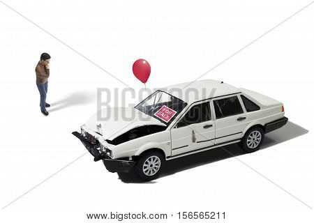 Still Life of a Toy Man Looking at Automobile For Sale on White Background