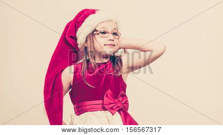 Christmas holiday concept. Toddler girl posing wearing Santa Claus hat and christmassy dress.