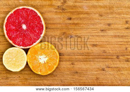 Sliced Grapefruit, Orange And Lemon On Wood Board