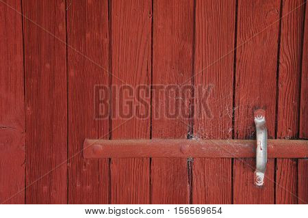 Hardly used red barn door with cobwebs in afternoon light