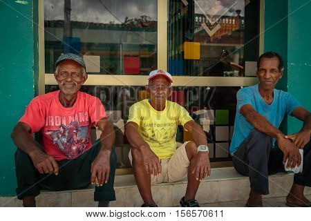 Cayo Coco island, Moron town, Cuba, July 23, 2013, Three seniors cuban man sitting together near the store and relaxing on sunny warm day in little town of Cayo Coco island