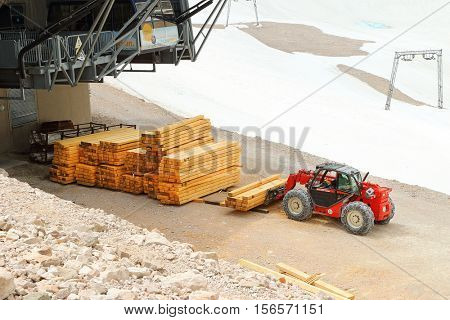 ZUGSPITZE GERMANY - JULY 5, 2016: Any unidentified carpenter with loader working on Germany's highest construction site in 2962m. Building the new Zugspitze cable car for tourists and skiers.
