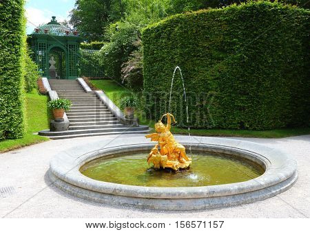 LINDERHOF GERMANY - JULY 8, 2016: A golden fountain in Linderhof Palace garden. Castle in southwest Bavaria near Garmisch Partenkirchen. The Castle built by King Ludwig II of Bavaria in 19th century.