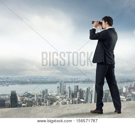 Businessman looks at the city from the roof with binoculars