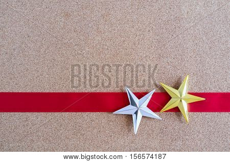Christmas Golden And Silver Stars And Red Ribbon On Cork Board.