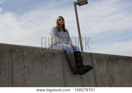 A young lady sits on a concert wall with a boot on
